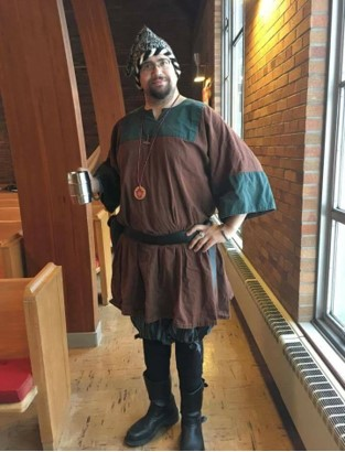 Man in medieval tunic holding a mug