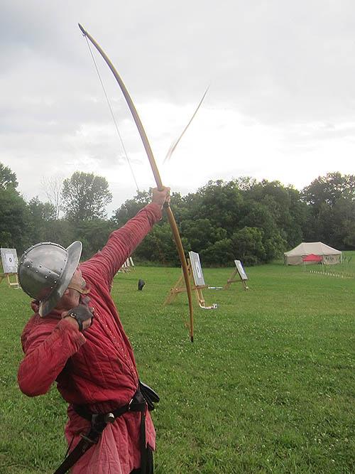 man shooting an arrow from a longbow