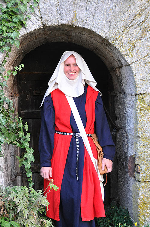 woman in medieval garb standing in arched stone passageway