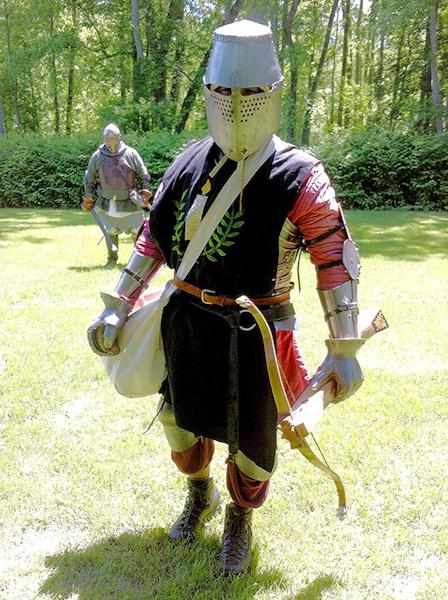Man in armor holding a crossbow.