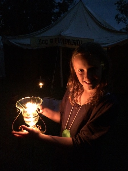 Girl holding a lit oil lamp.