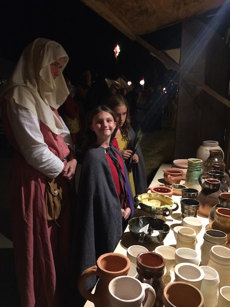 A woman and two girls in medieval dress admiring a potter's wares.