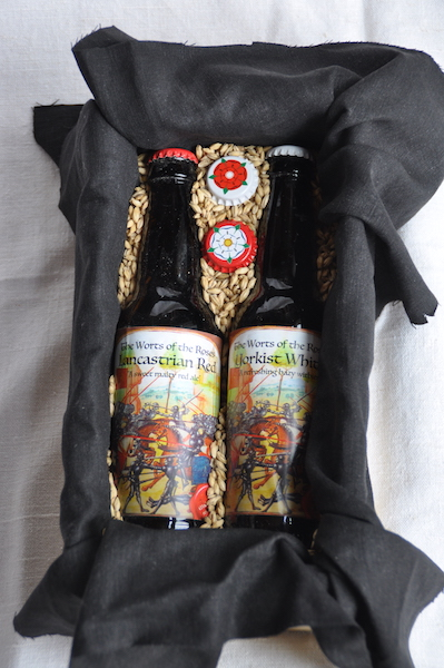 Two bottles of beer with medieval labels and rose-themed caps.