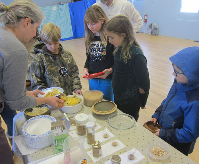 Four children in line for food with medieval spices.