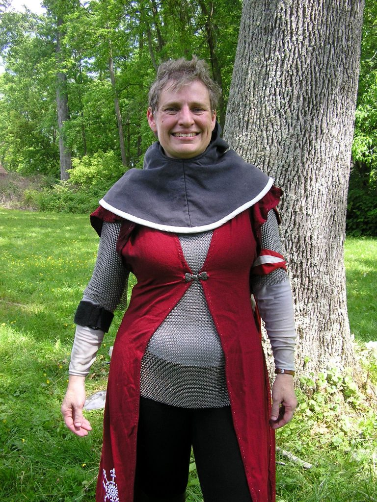 Woman in fencing gear, including a mail shirt.
