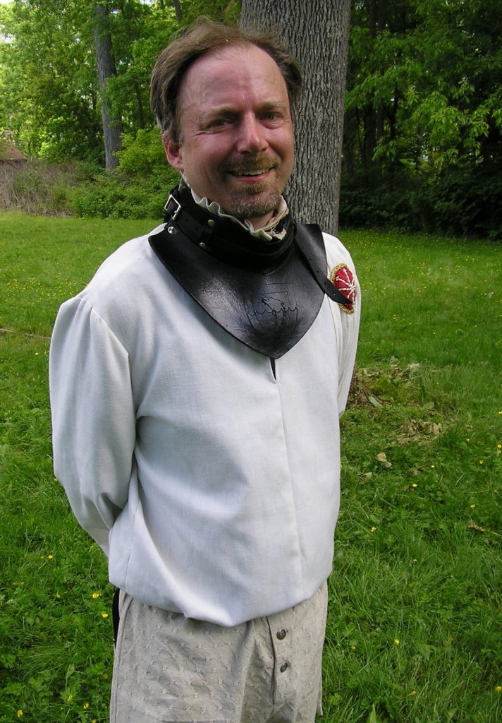 Man wearing fencing jacket and throat protection.
