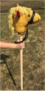 Hobby horse with yellow head, red ears, and leather bridle, held by a child.